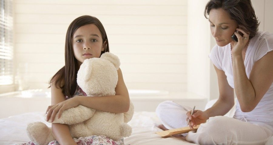 Mother-Using-Cellphone-With-Daughter-Holding-Teddy-Sitting-On-Bed-900x480