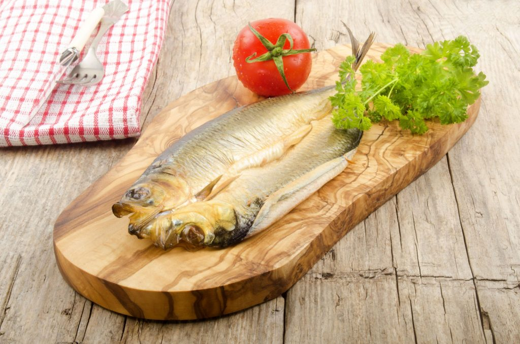 47986880 - smoked kipper with tomato and parsley on a wooden board