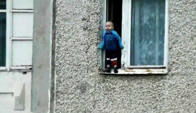 Îţi taie respiraţia! Un copil de doi ani filmat în timp ce stă pe fereastra unui bloc