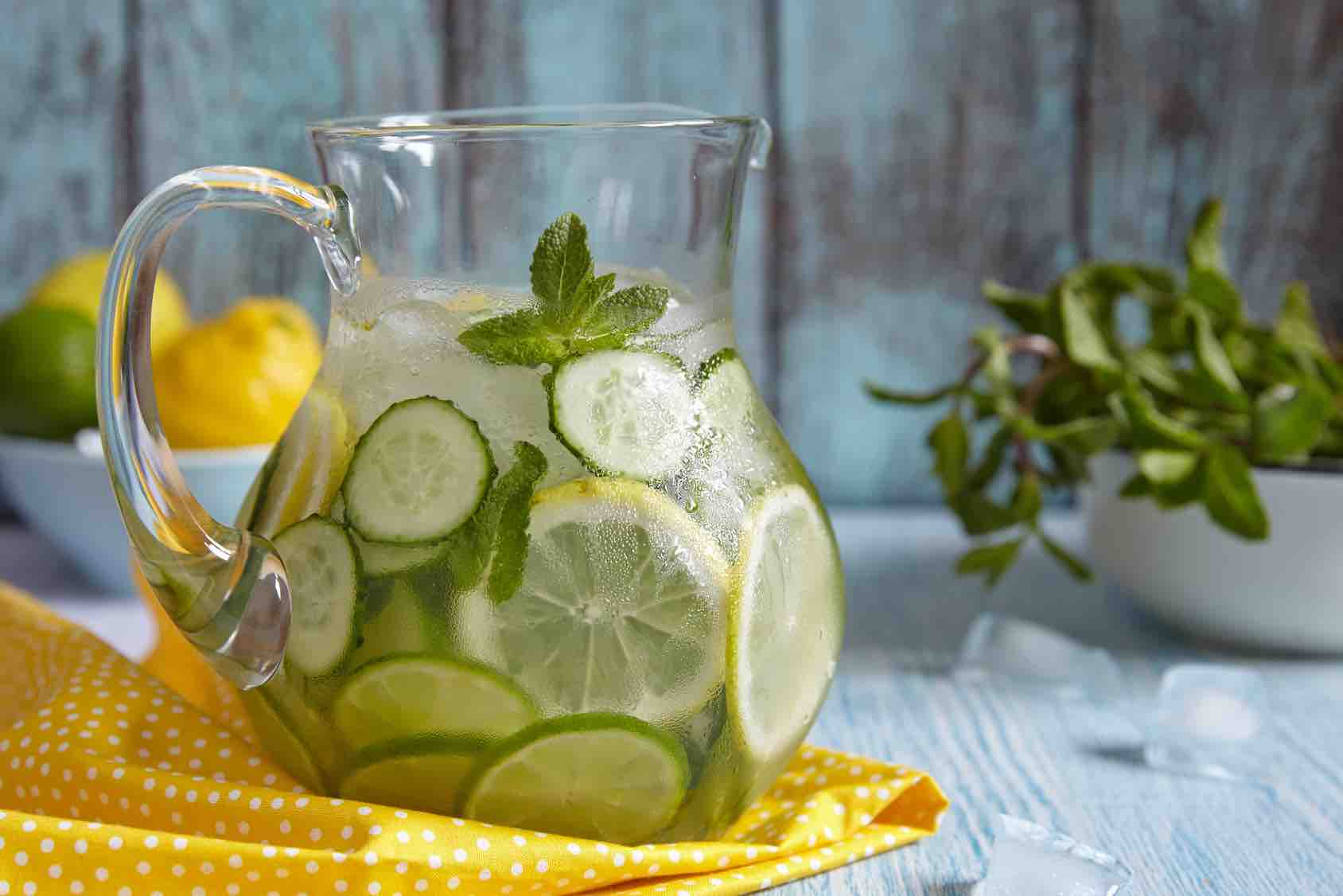 Fruit water with lemon, lime, cucumber and mint in glass pitcher