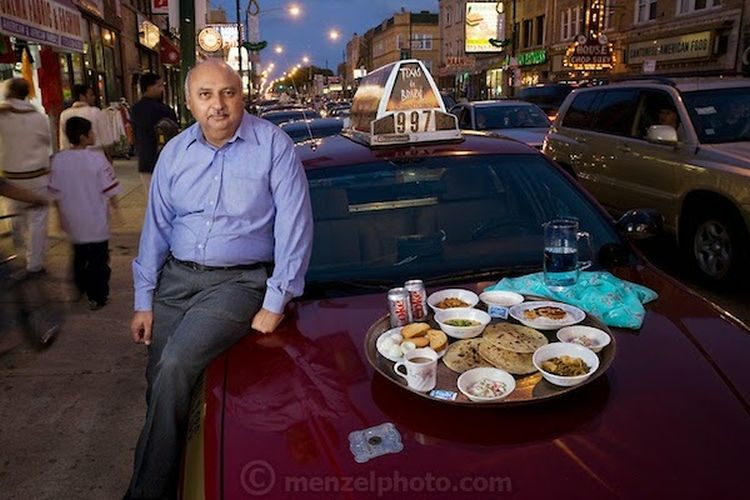 """Din Memon, a Chicago taxi driver, with his typical day's worth of food arranged on the hood of his leased cab on Devon Avenue in Chicago, Illinois. (From the book What I Eat: Around the World in 80 Diets.) The caloric value of his day's worth of food in the month of September was 2,000 kcals. He is 59 years of age; 5 feet, 7 inches tall; and 240 pounds. Din came to the United States as a young man in search of freedom and opportunity and remains pleased with what he found. He has lived in Chicago for 25 years and has been driving a cab for the past two decades, five to six days a week, 10 hours a day. He knows where all of the best Indian and Pakistani restaurants are throughout Chicago, but prefers his wife's home cooking above all. His favorites? """"Kebabs, chicken tika, or biryani—spicy food,"""" he says. Tika is dry-roasted marinated meat, and biryani is a rice dish with meat, fish, or vegetables that is highly seasoned with saffron or turmeric. MODEL RELEASED."""