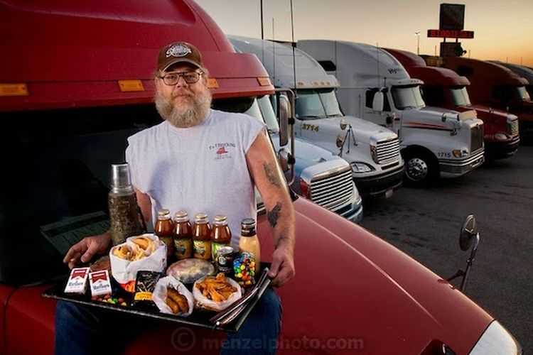 USA The Long Haul Trucker Conrad Tolby, an American long-distance truck driver, photographed with a typical day's worth of food on the cab hood of his semi tractor trailer at the Flying J truck stop in Effingham, Illinois. The caloric value of his meals this working weekday was 5,400 kcals. At the time of the photograph Tolby was 54 years of age; 6 feet, 2 inches tall; and weighed 260 pounds. His meals on the road haven't changed much over the years—truck stop and fast-food fare, heavy on the grease—despite warnings from his doctor. He has more reason than most to watch his diet, as he's suffered two heart attacks—both in the cab of his truck. The trucker travels with his best friend and constant companion, a five-year-old shar pei dog, named Imperial Fancy Pants, who gets his own McDonald's burger and splits the fries with Conrad. From the book What I Eat: Around the World in 80 Diets. (Please note that the calorie total is not a daily caloric average. See his chapter, and the methodology, in the book for more information). MODEL RELEASED. Note: The authors used a typical recent day as a starting point for their interviews with 80 people in 30 countries. They specifically chose not to cover daily caloric averages, as they wanted to include some extreme examples of eating, like one woman's diet on a bingeing day or the small number of calories a herder in Kenya ate during extreme drought. The texts in the book provide the context for the photographs, detailing each person's diet, culture, and circumstance at the moment they were photographed: a snapshot in time. A complete methodology is available in the book.
