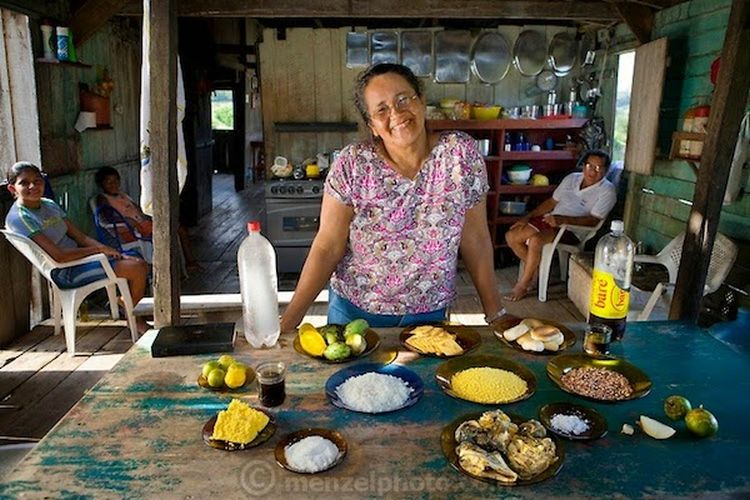Solange Da Silva Correia, a rancher's wife, with family members in their house overlooking the Solimoes River, with her typical day's worth of food. (From the book What I Eat: Around the World in 80 Diets.) The caloric value of her day's worth of food on a typical day in the month of November was 3400 kcals. She is 49 years of age; 5 feet 2.5 inches tall; and 168 pounds. She and her husband, Francisco (sitting behind her, at right), live outside the village of Caviana with three of their four grandchildren in a house built by his grandfather. They raise cattle to earn income—and sometimes a sheep or two to eat themselves—but generally they rely on their daily catch of fish, and eggs from their chickens, for animal protein. They harvest fruit and Brazil nuts on their property and buy rice, pasta, and cornmeal from a store in Caviana. They also purchase Solange's favorite soft drink made from guarana—a highly caffeinated berry indigenous to the country. MODEL RELEASED.