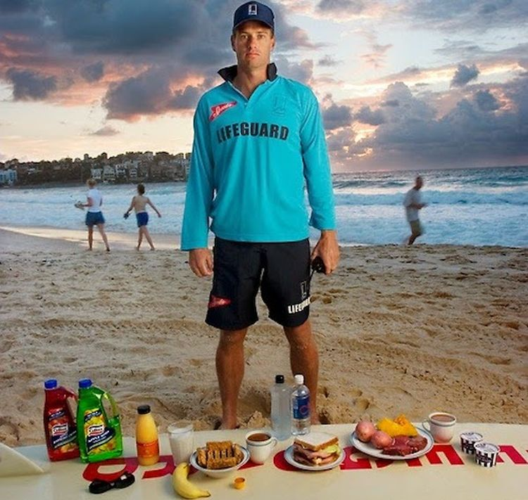 Bruce Hopkins, a Bondi Beach lifeguard, with his typical day's worth of food in Sydney, New South Whales, Australia. (From the book What I Eat: Around the World in 80 Diets.) The caloric value of his day's worth of food on a typical day in the month of February was 3700 kcals. He is 35 years of age; 6 feet tall, and 180 pounds. Hopkins eats moderately, rarely—if ever—eats fast food, and drinks alcohol only when he and his wife go to dinner with friends. MODEL RELEASED.