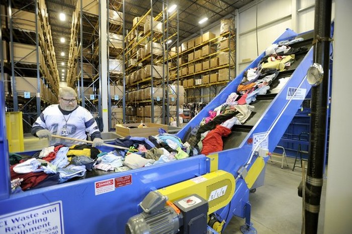 Wed. , Feb. 8, 2012. Ron Moran feeds a baler inside Goodwill's new warehouse and buy the pound outlet store at the Gorham Industrial Park. (Photo by John Patriquin/Portland Press Herald via Getty Images)