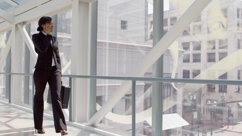 Horizontal shot of a businesswoman, talking on a cellphone, walking through a skybridge
