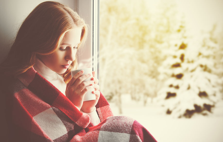 46636841 - pensive sad girl with a warming drink looking out the window in the winter forest