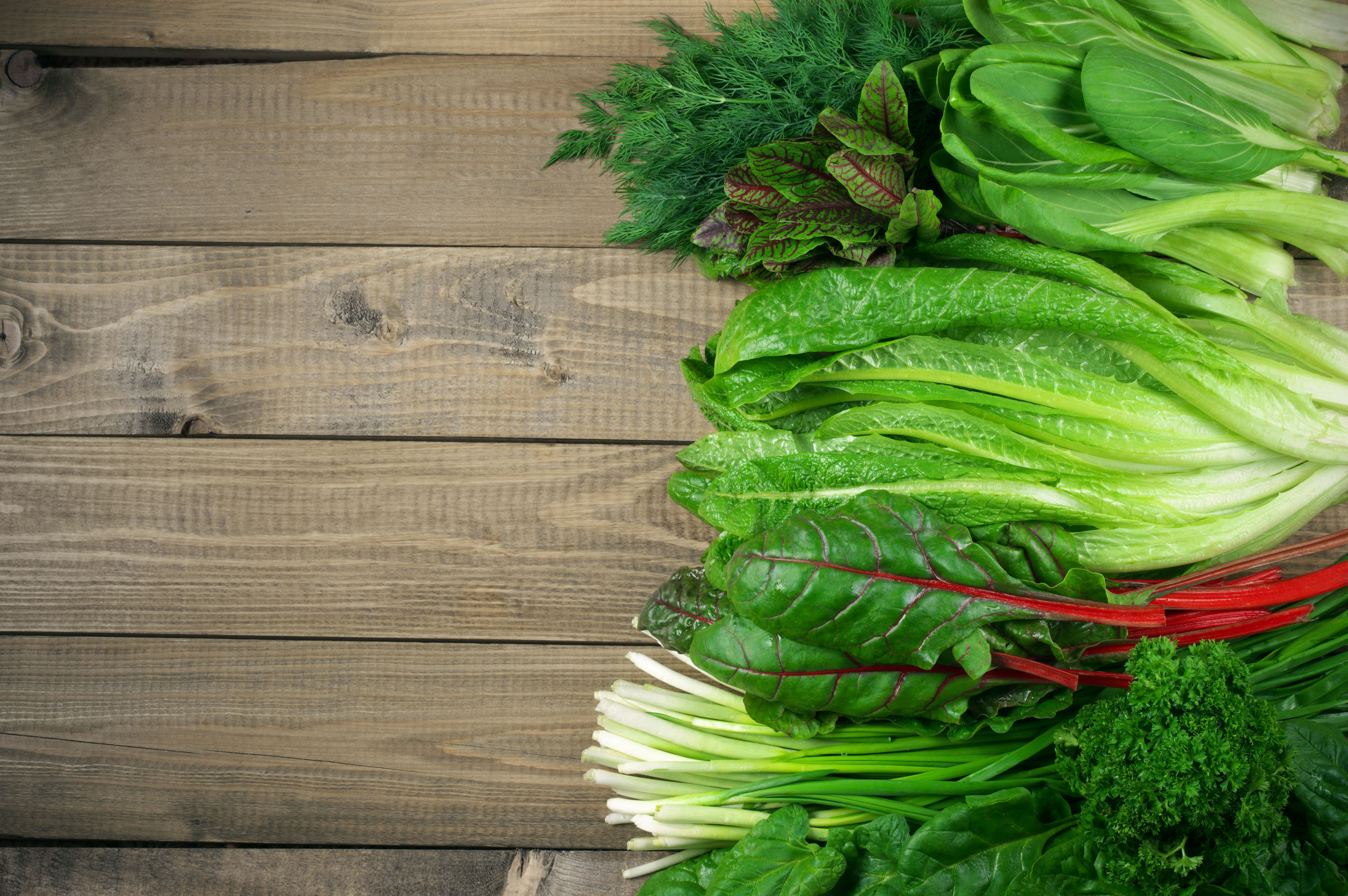 53308576 - spring vitamin set of various green leafy vegetables on rustic wooden table. top view point.