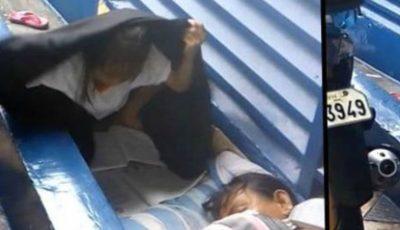 O fetiță a fost surprinsă în timp ce încerca să își facă temele în ploaie, sub o pătură