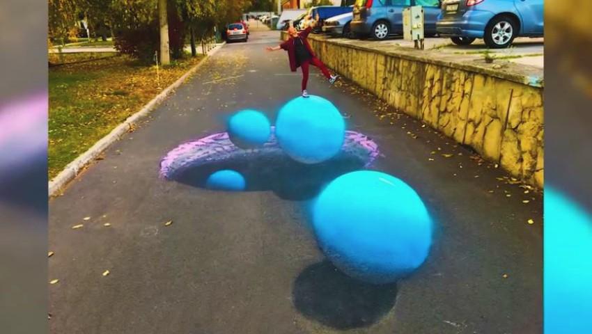 Creația unei pictorițe din Capitală! A realizat, pe asfalt, un impresionant desen 3D care ilustrează niște planete
