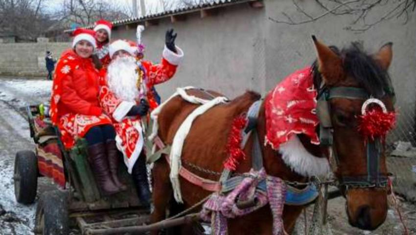 Foto: O femeie din Găuzeni a îmbrăcat costumul tradițional și a devenit Moș Crăciun pentru toți copiii din localitatea sa