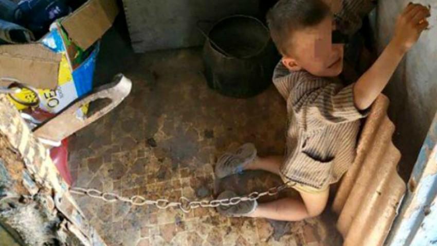 Foto: Înfiorător. Un copil de 6 ani, ținut legat cu lanțuri și bătut de tatăl său