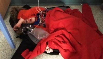 Copil bolnav care așteaptă întins pe jos, pe holul unui spital din Marea Britanie
