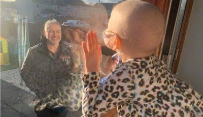 Imaginea emoționantă a unei fetițe bolnave de cancer, izolată de tată pentru a o proteja în fața epidemiei de coronavirus