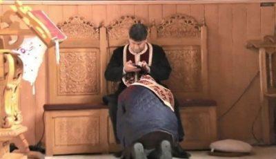 Un preot filmat cum butonează telefonul, în timp ce o creştină i se spovedeşte