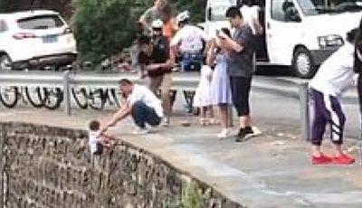 Un tată și-a ținut copilul pe marginea unei stânci, pentru a-i face o poză