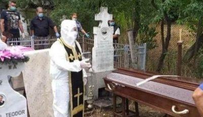 Preot îmbrăcat în combinezon la o slujbă de înmormântare. Foto