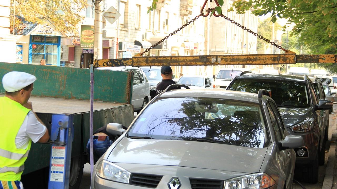 Foto: Mai multe automobile parcate pe o stradă din centrul Capitalei au fost ridicate și evacuate la parcarea specială de la Trușeni